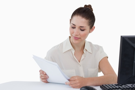 Smiling businesswoman looking a document against a white background Stock Photo - 16069821