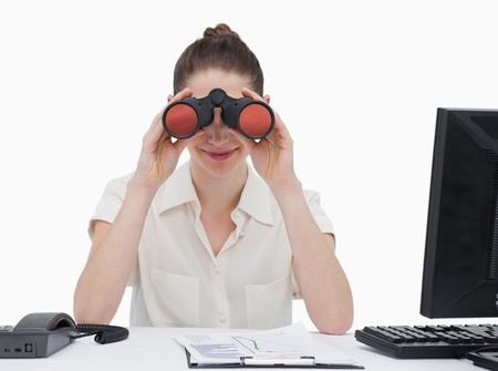 Businesswoman looking through binoculars against a white background photo