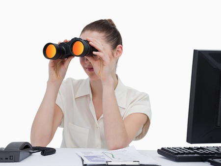 Young businesswoman looking through binoculars against a white background photo