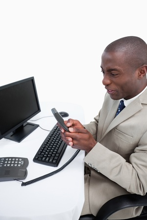 Portrait of an angry businessman talking to the phone while using a monitor against a white background photo