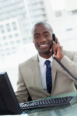 councilor: Portrait of a smiling office worker making a phone call  while using a computer Stock Photo