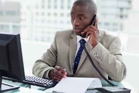 Entreprenör ringer medan du tittar på sin dator på sitt kontor