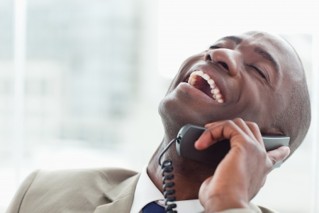 Close up of a delighted businessman on the phone in his office photo