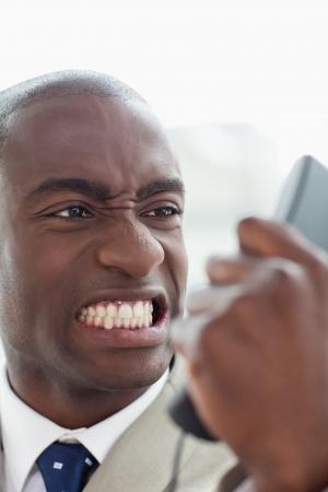 phone handset: Ritratto di un uomo d'affari arrabbiato guardando il suo telefono cellulare nel suo ufficio Archivio Fotografico