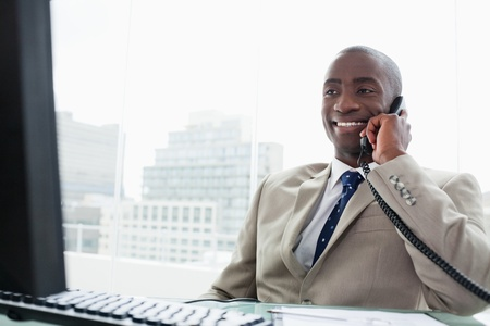 Smiling businessman on the phone in his office photo