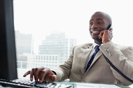 councilor: Businessman on the phone while using a computer in his office Stock Photo