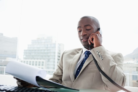 Businessman on the phone while reading a document in his office Stock Photo - 16075406