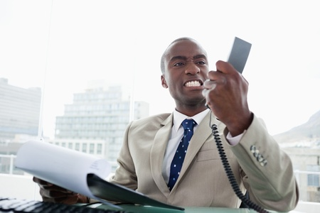 phone handset: Uomo d'affari arrabbiato guardando il suo telefono cellulare nel suo ufficio