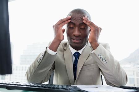 Uitgeput ondernemer het werken met een computer in zijn kantoor Stockfoto