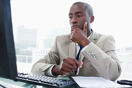 Serious entrepreneur while working with a computer in his office Stock Photo