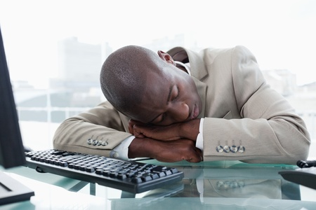 Businessman sleeping on his desk in his office photo