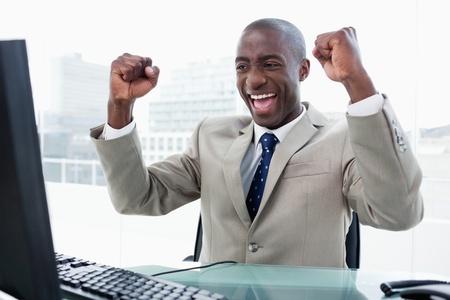 using the computer: Exitoso hombre de negocios trabajando con un ordenador en su oficina