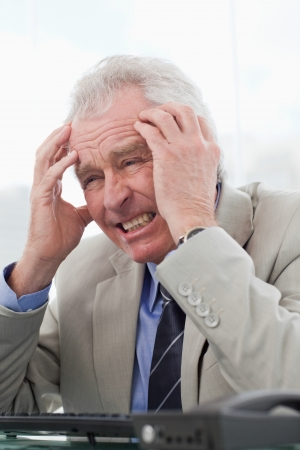Portrait of a senior manager having a headache in his office photo
