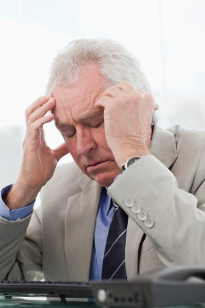 Portrait of an exhausted senior manager having a headache in his office photo