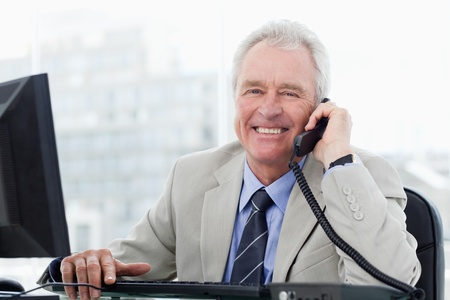 councilor: Smiling senior manager on the phone in his office