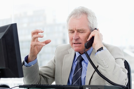 Irritated senior manager on the phone in his office photo