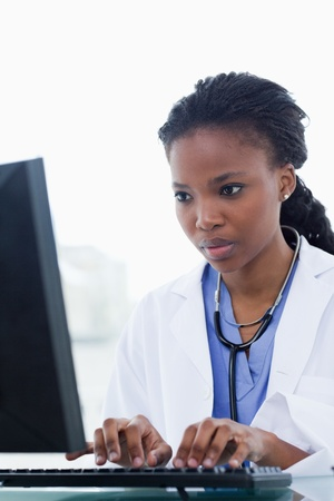 doctor computer: Portrait of a female doctor using a computer in her office Stock Photo
