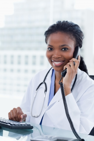 black nurse: Portrait of a female doctor on the phone in her office
