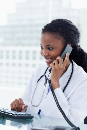 Portrait of a female doctor on the phone while using a computer in her office photo
