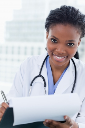 woman doctor: Portrait of a smiling female doctor signing a document in her office Stock Photo