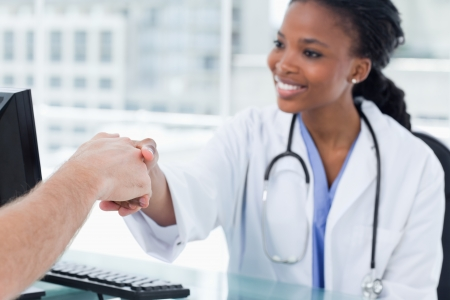 Smiling female doctor shaking a hand in her office photo