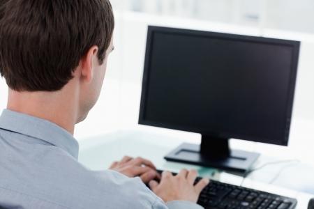monitor de computadora: Vista trasera de un empresario que trabaja con una computadora en su oficina Foto de archivo