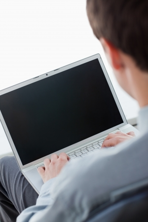 Back view of a businessman typing on a laptop against a white background photo