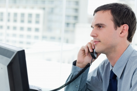 councilor: Young office worker on the phone`in his office Stock Photo