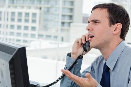 persona confundida: Confundido empleado de oficina en el teléfono en su oficina