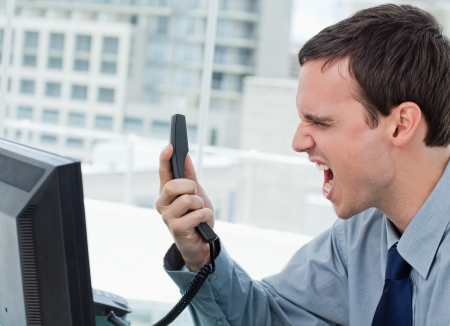 Angry office worker on the phone in his office photo