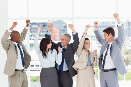 Smiling business people looking at each other and raising their arms in success photo