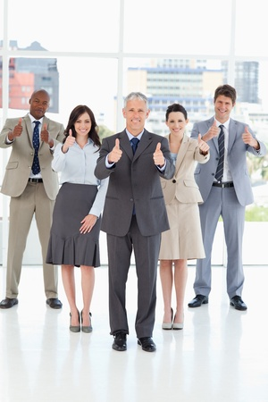 thumbsup: Smiling business team standing together with their thumbs up in success