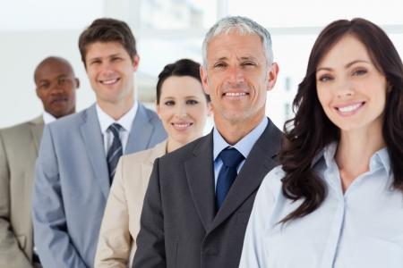 liderazgo: Cuatro empleados sonrientes de pie alrededor de su gerente Foto de archivo
