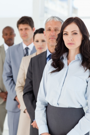 Young serious executive woman standing upright in front of her co-workers photo
