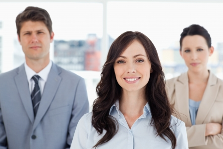 Young smiling woman standing in front of two business people Stock Photo - 16185458