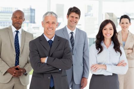 negocios internacionales: Sonriente y equipo de negocios conf�a en pie frente a una ventana luminosa