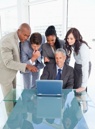 Young smiling executives attentively looking at the laptop screen Stock Photo - 16236174