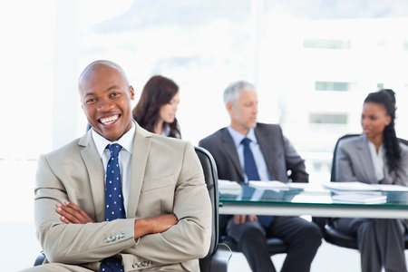 Young executive laughing while crossing his arms and sitting\ in front of his team