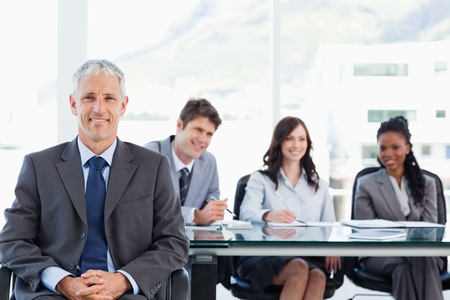 Mature smiling manager sitting in front of his team with his hands crossed Stock Photo - 16185451