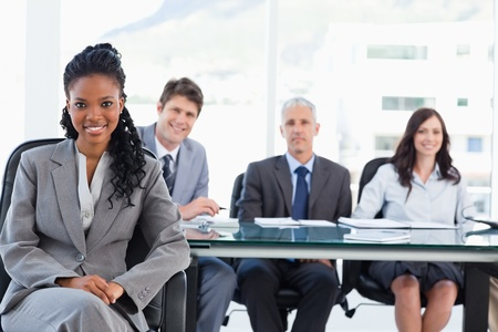 project manager: Young executive woman smiling while sitting with her legs crossed and her hands on her leg
