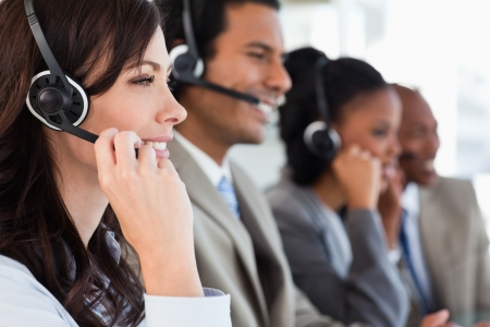 call center office: Young employee working with a headset and accompanied by her team Stock Photo