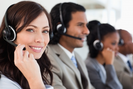 customer support: Smiling worker doing her job with a headset while looking at the camera
