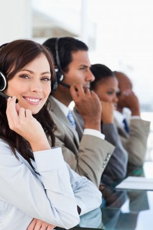 trabajando duro: Joven sonriente agente del centro de llamadas mirando a la c�mara mientras se trabaja duro