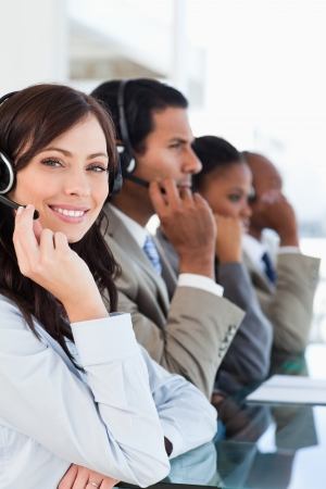 Young smiling call centre agent looking at the camera while working hard Stock Photo - 16236157