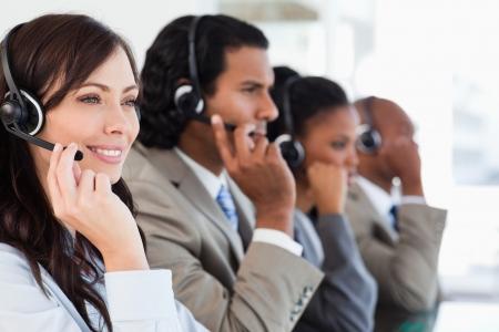 trabajando duro: Joven sonriente empleado de call center trabajando duro y acompa�ada por su equipo