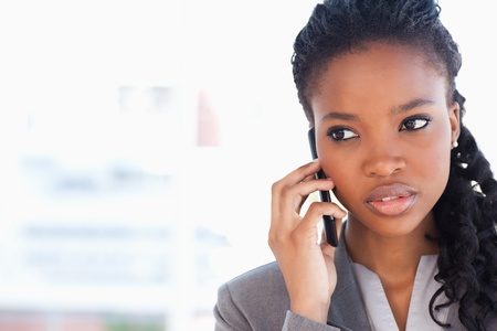 woman window: Young employee talking on the phone while looking towards the side Stock Photo