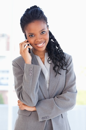 Smiling employee standing upright seriously and talking on a phone with her arms crossed photo