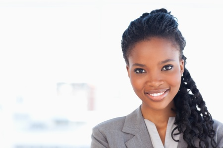 young women only: Smiling employee standing upright in front of a window while wearing a formal suit
