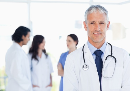 Mature doctor standing upright in front of his interns photo