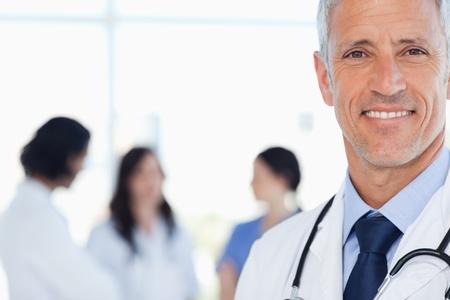Doktor som visar en strålande leende med hans medicinska praktikanter bakom honom